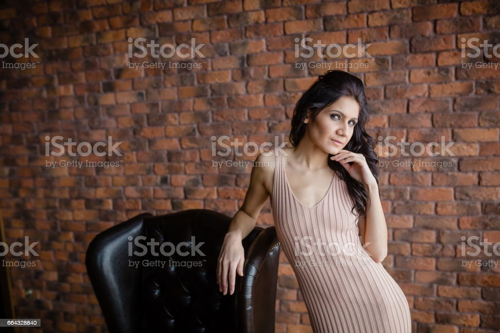 Tall slender brunette next to a armchair stock photo