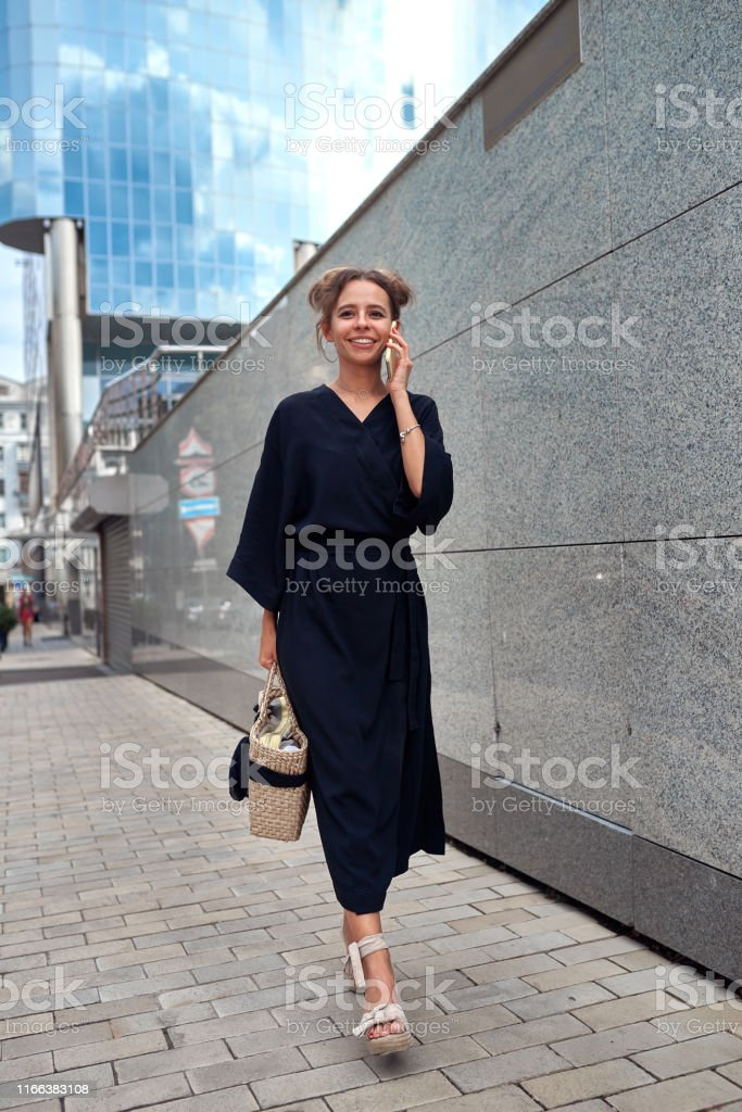 Slender girl in a black dress walking down the street and talking on...