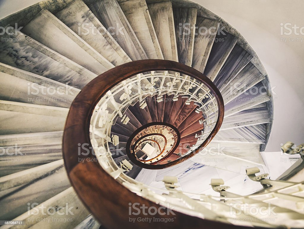 Tall spiral staircase with marble steps and wooden banister stock photo