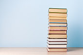 istock A tall stack of books stands on a wooden table against a light blue wall, space for text 1258065804