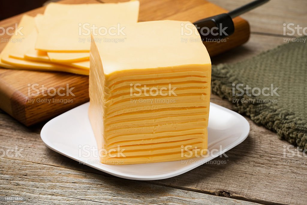 Tall stack of orange cheese on white plate royalty-free stock photo