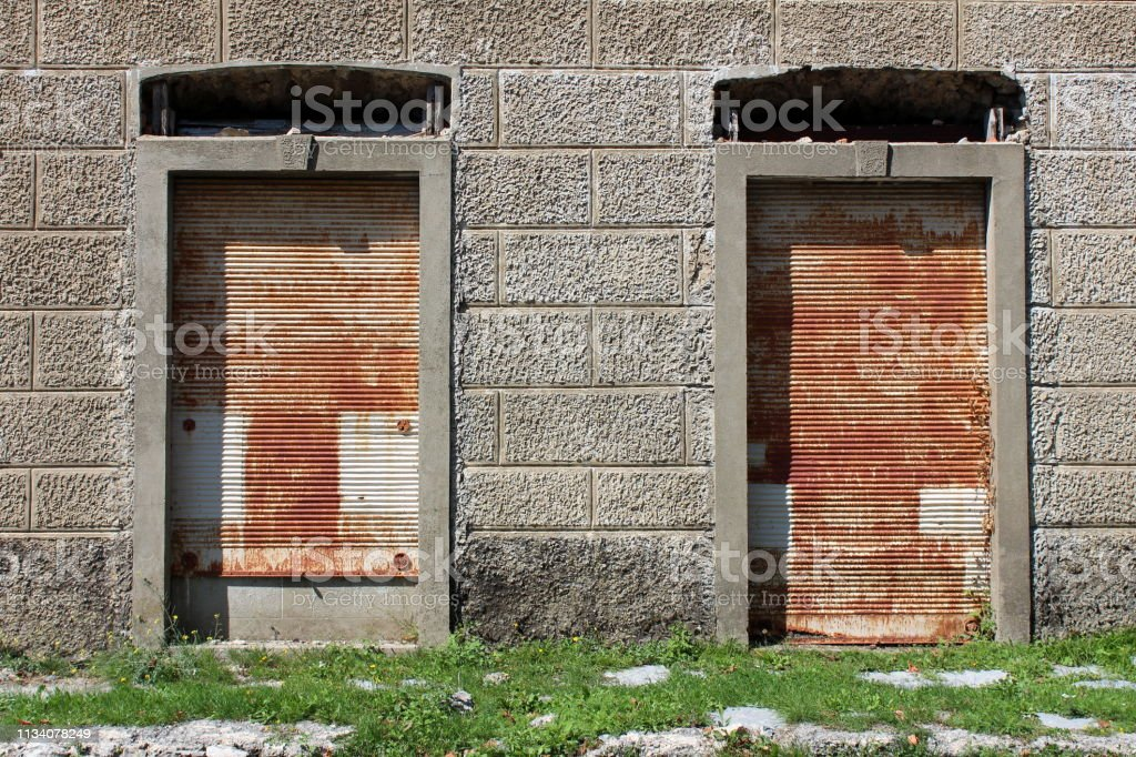 Tall store windows covered with rusted metal roll up blinds on...