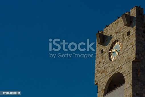 Tower of bricks against a blue sky with a bright sunlight for a clock with place for text. The time on the clock is four hours and forty-five minutes. Large dial of an old mechanical watch in Europe.