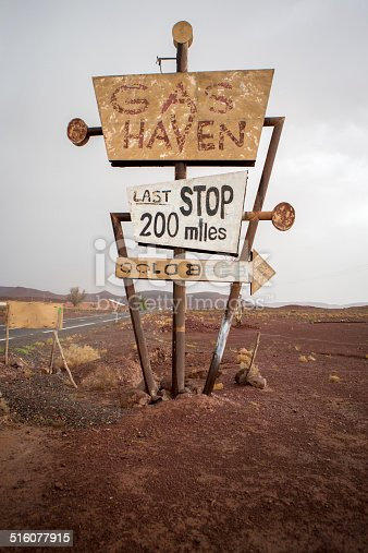 Tall vintage and abandoned gas sign standing along the deserted road to Ouarzazatein in Morocco.