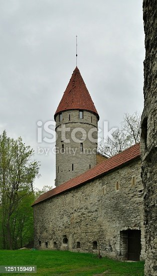 A conical tile roof over a turret and wall, all constructed of stone, was part of the defensive fortification for Tallinn, Estonia.