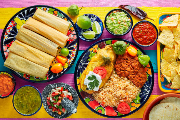 tamale with corn leaf and filled chili pepper - mexican food stock photos and pictures