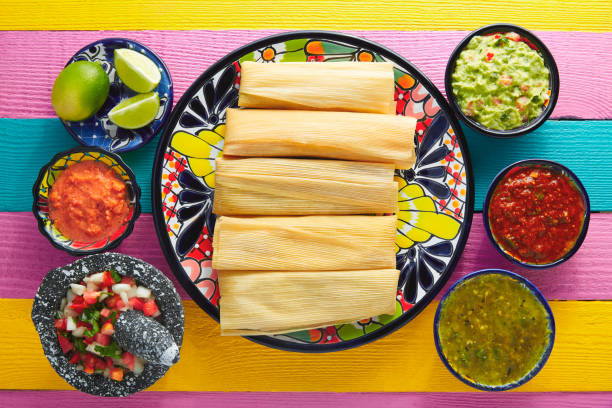 Tamale with corn leaf and sauces guacamole Tamale with corn leaf and sauces guacamole pico de gallo mexican culture stock pictures, royalty-free photos & images