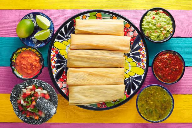 tamale mit mais blatt und saucen guacamole - mexikanische möbel stock-fotos und bilder