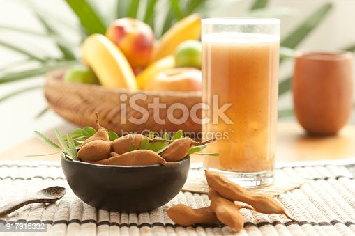 Group of tamarind fruit pods and leafs in bowl with tamarind juice glass and a basket with fruits in the background. No people. Horizontal composition photography. Still life. Organic. Vegan or vegetarian food. Healthy eating. Antioxidant. Front view. Outdoors. Natural daylight.