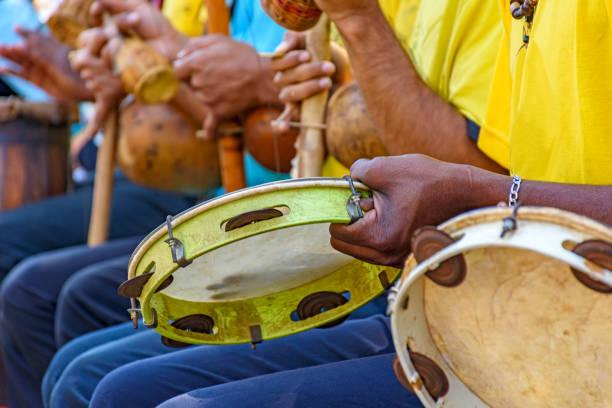 tambourine, berimbau e outro jogador dos instrumentos durante a apresentação de capoeira brazilian - nordeste - fotografias e filmes do acervo