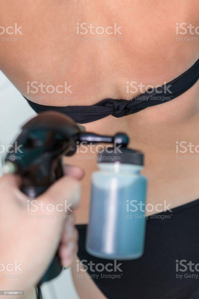 Tan spray ser aplicado às costas de mulher na cabine de bronzeamento - foto de acervo