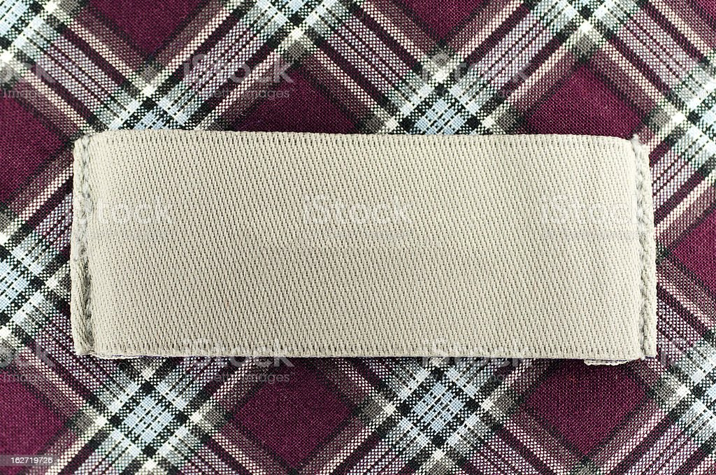 Tan tag on the collar of a red plaid patterned shirt stock photo