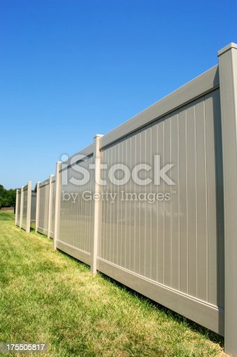 Tan vinyl fence running across a yard with blue sky in the background