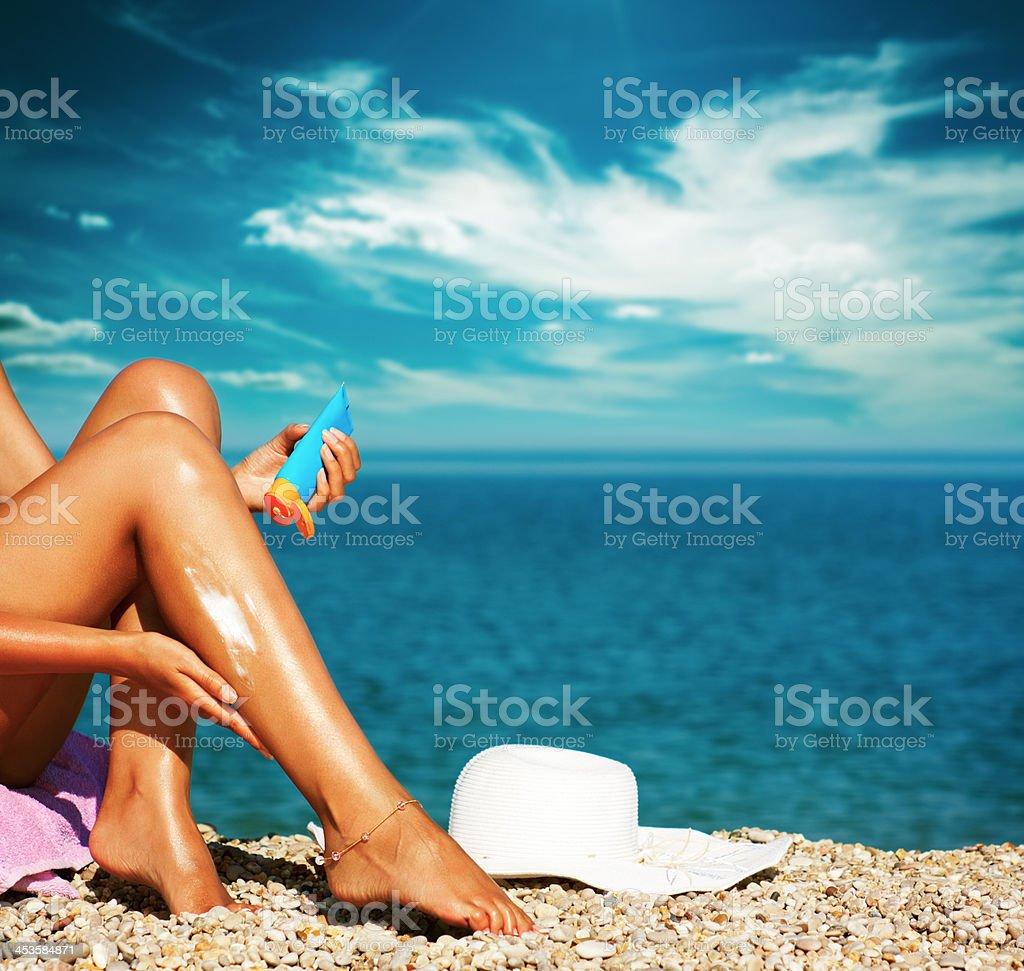 Tan Woman Applying Sunscreen on Legs stock photo