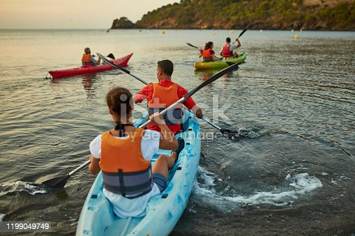 Spanish male and female kayakers in 30s and 40s beginning early morning paddling excursion in Mediterranean Sea off the Costa Brava.