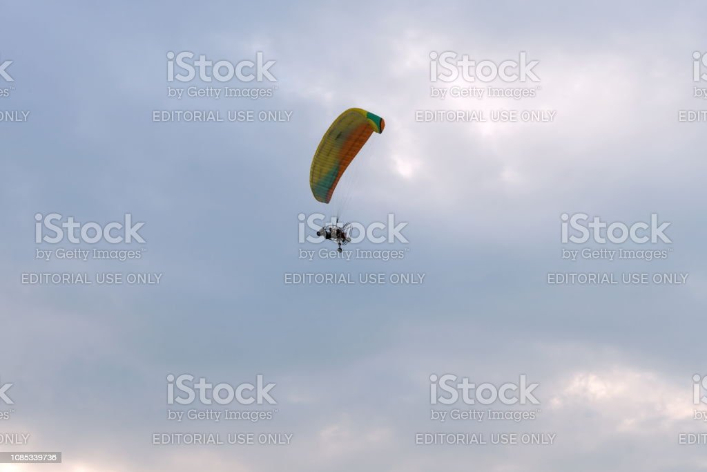 A Tandem Motor Paraglider Flies Through The Evening Cloudy