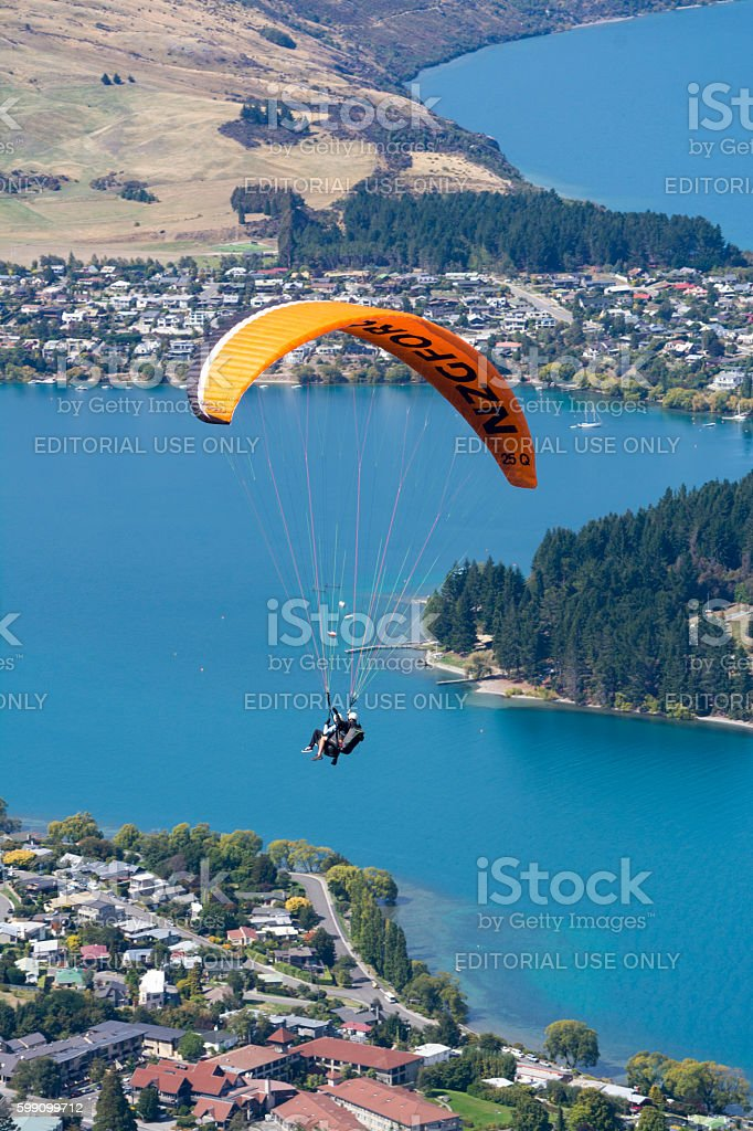 Tandem paragliding over Lake Wakatipu in Queenstown, New Zealand stock photo