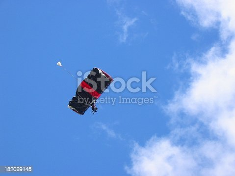 tandem skydivers floating towards clouds.