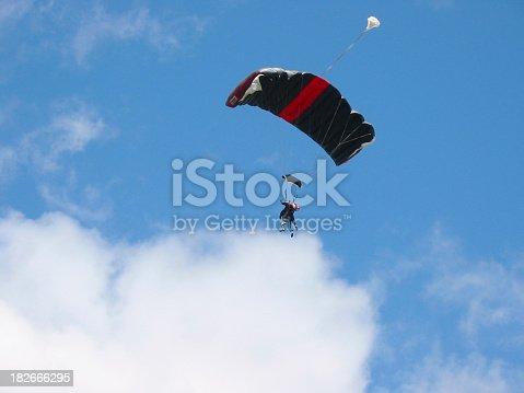 tandem skydivers drifting towards clouds.