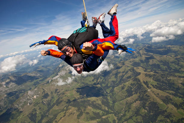 Tandem skydivers plunge through lofty skies above mountains Tandem skydivers plunge through lofty skies taking the plunge stock pictures, royalty-free photos & images