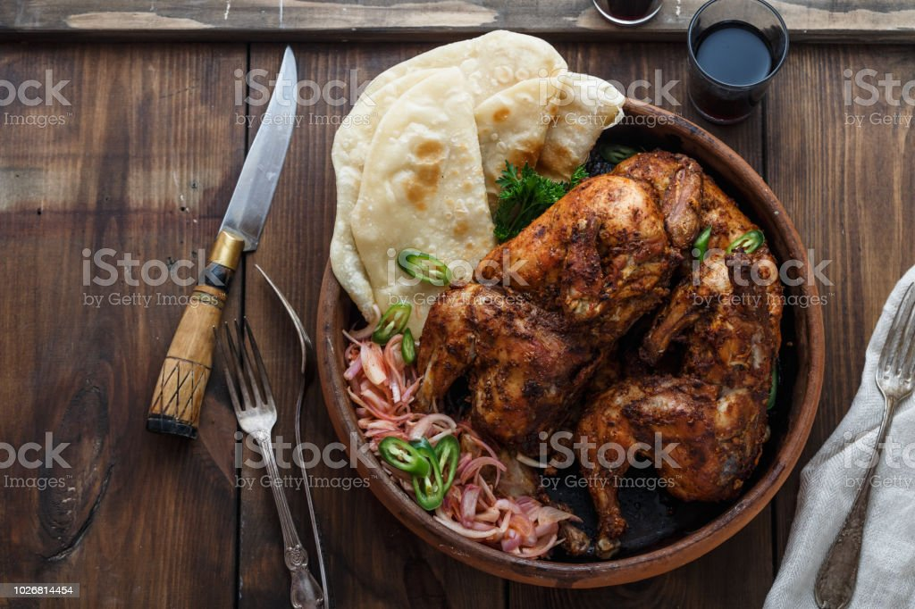 Tandoori chicken. Half of tandoori chicken served with lime slices and cilantro. Top view, blank space stock photo