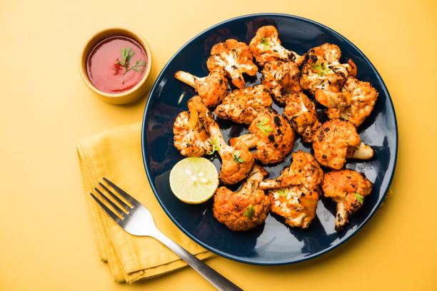 tandoori gobi / gebratene blumenkohl tikka ist eine vorspeise essen aus indien. mit ketchup serviert. selektiven fokus - gebackener blumenkohl stock-fotos und bilder