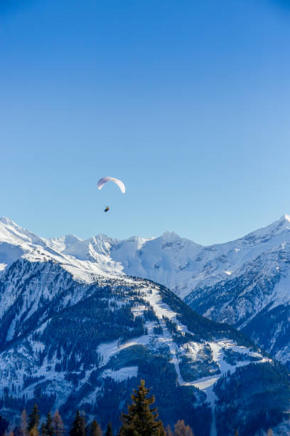 Tandum paragliders float above the rough snow covered mountains below stock photo