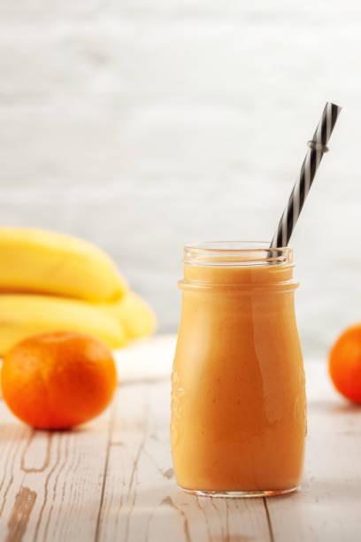 tangerina e smoothie de banana em mesa de madeira - squeeze bottle - fotografias e filmes do acervo