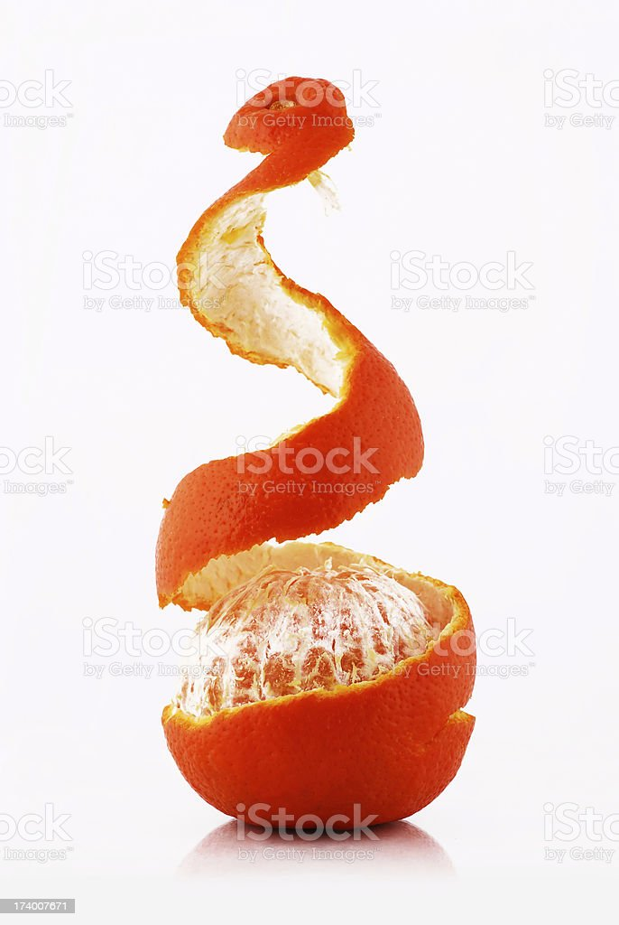 Tangerine being pealed over a white background stock photo