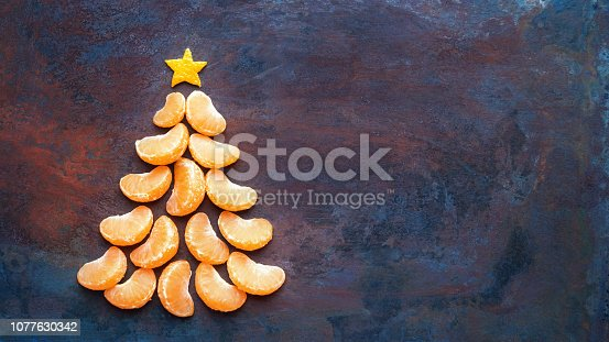 istock Tangerine christmas tree  on dark rust metal grunge background. Xmas festive greeting card with a tree of orange tangerine slices and star, copy space, flat lay 1077630342