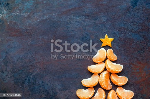 istock Tangerine christmas tree  on dark rust metal grunge background. Xmas festive greeting card with a tree of orange tangerine slices and star, copy space, flat lay 1077630344
