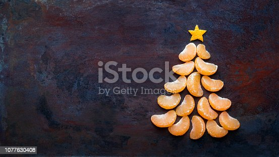 istock Tangerine christmas tree  on dark rust metal grunge background. Xmas festive greeting card with a tree of orange tangerine slices and star, copy space, flat lay 1077630408
