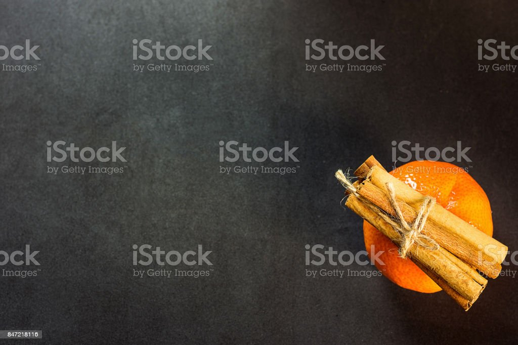 Tangerine Cinnamon Sticks tied with Twine on Black Background Christmas New Year Greeting Card Poster Copy Space Top View Flat Lay stock photo