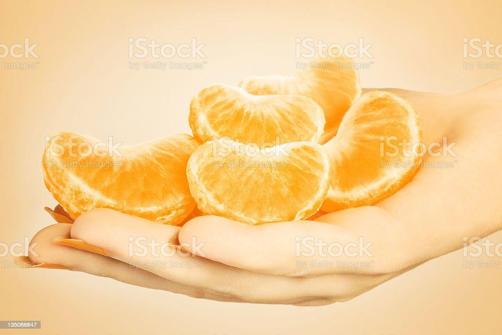 Tangerine slice. Hand with mandarin royalty-free stock photo