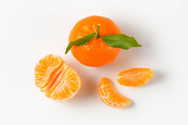 tangerine with separated segments whole tangerine with separated segments on white background tangerine stock pictures, royalty-free photos & images