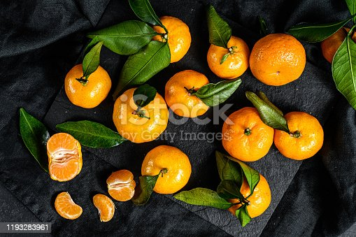 Tangerines, mandarines  with leaves. Black background. Top view.
