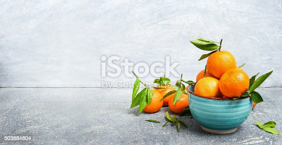 Fresh Tangerines with green leaves in blue bowl over rustic background, side view, banner
