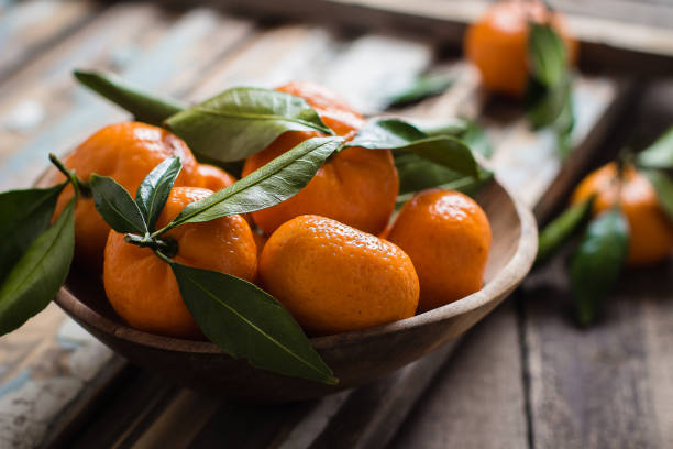 Tangerines (mandarins or citrus fruits) with leaves in wooden bowl on rustic wooden background, copy space Tangerines (mandarins or citrus fruits) with leaves in wooden bowl on rustic wooden background, copy space tangerine stock pictures, royalty-free photos & images