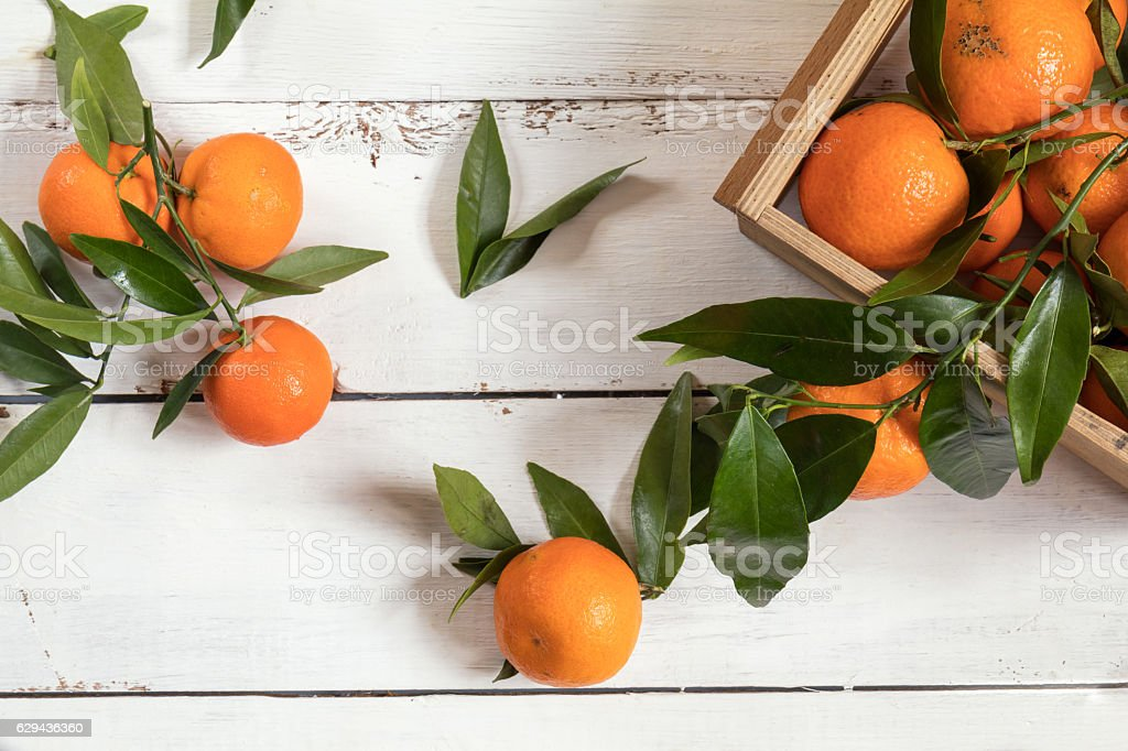 Tangerines with leaves on white wooden table stock photo