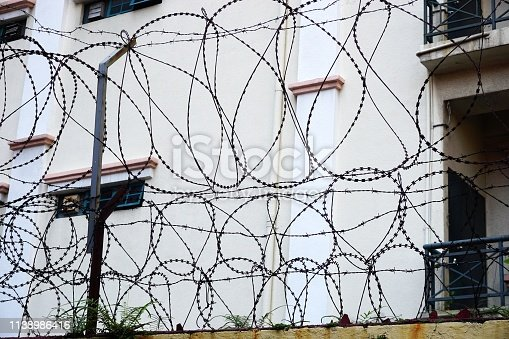 Loops of sharp barbed razor wire form a secure barrier atop a wall in urban Southeast Asia