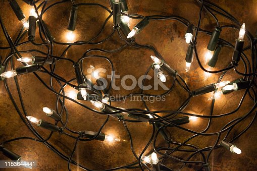 Top view of tangled Christmas string lights shot on abstract brown background.
