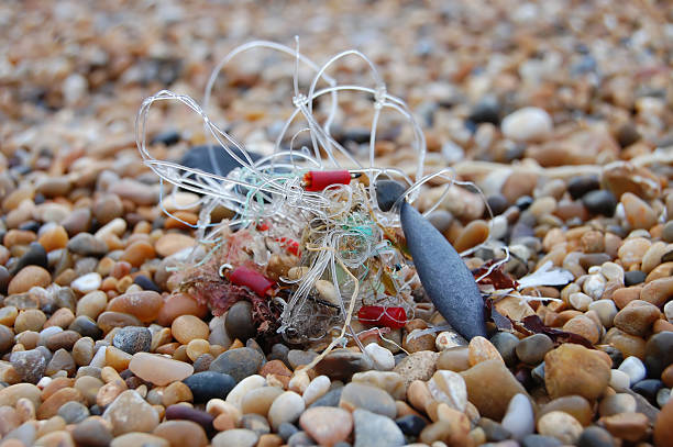 Tangled Fishing Line Tangled fishing line on a pebble beach fishing line stock pictures, royalty-free photos & images