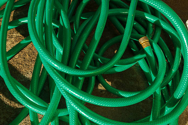 tangled green hose pipe - garden hose stock pictures, royalty-free photos & images