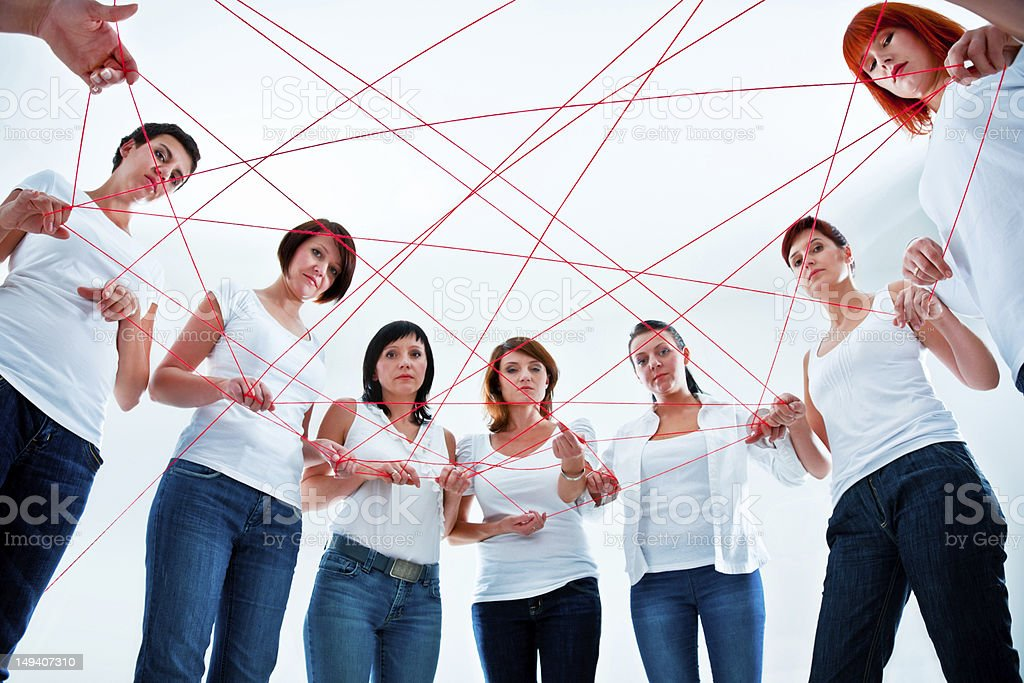 Tangled in the network Network concept. Group of women holding red rope. Adult Stock Photo