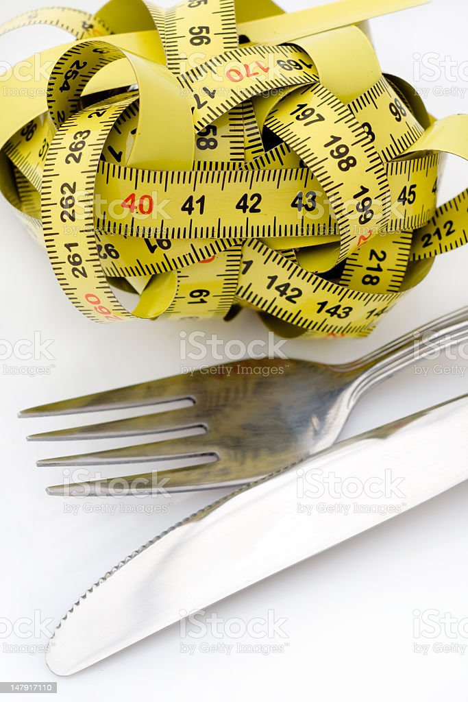 Tangled up tape measure next to a fork and knife royalty-free stock photo
