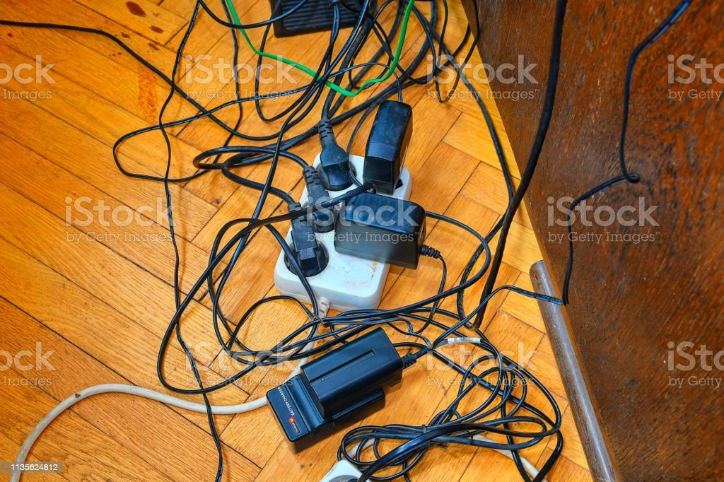 Tangled wires and battery charges on parquete floor. Domestic appliances.  Wires mess in domestic room - fotografia de stock
