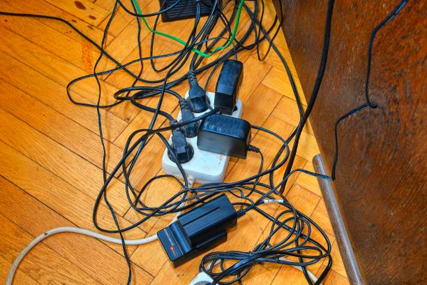 Tangled wires and battery charges on parquete floor. Domestic appliances.  Wires mess in domestic room stock photo