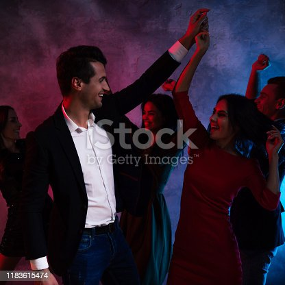 497317250 istock photo Tango dancers. A young smartly dressed couple is holding hands, while dancing with their three friends, celebrating New Year or Christmas Eve. 1183615474