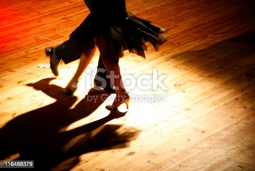 Twirling couple under the spotlights, in a colorful shot full of movement, taken during a latin dance night. Available light, high ISO, royalty free stock photo.