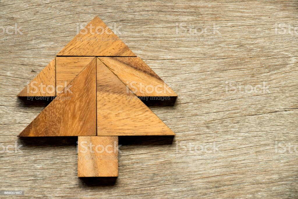 tangram puzzle in christmas tree shape on wood background royalty free stock photo
